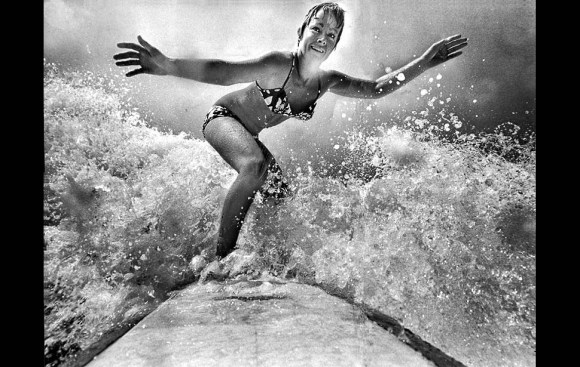 Feb. 24, 1970: Linda Benson, five-time world surfing champion, rides wave in front of her Hermosa Beach home.