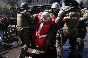 A demonstrator dressed as a Santa Claus is arrested by riot policemen during clashes with students protesting against the government to demand changes in the public state education system in Santiago, December 22, 2011. Chilean students have been protesting against what they say is the profiteering in the state education system. REUTERS/Ivan Alvarado (CHILE - Tags: POLITICS EDUCATION CIVIL UNREST)