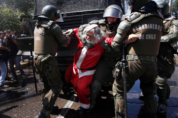 A demonstrator dressed as a Santa Claus is arrested by riot policemen during clashes with students in Santiago
